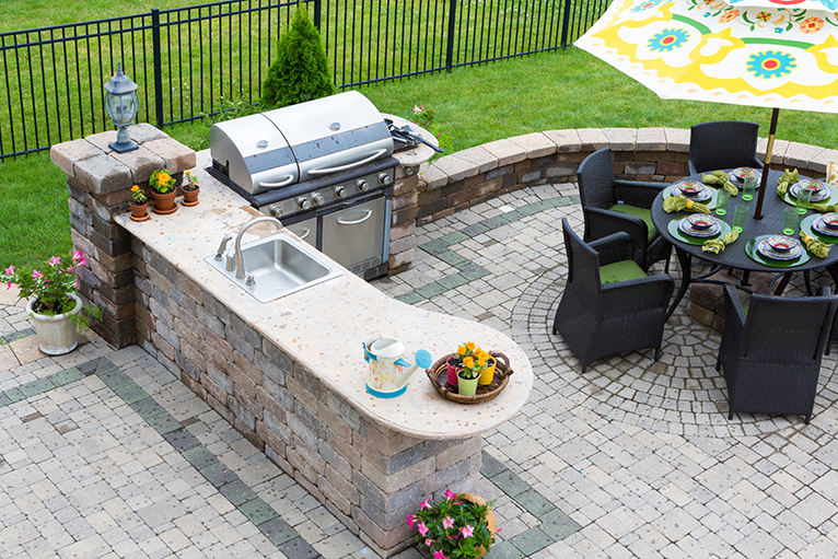 Garden with outdoor kitchen: sink, BBQ and seating area on paved patio