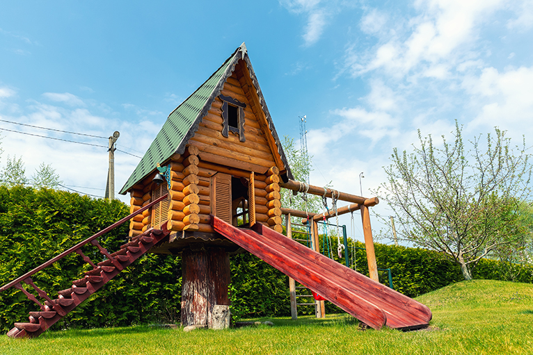 Wood treehouse with slide, swing and steps in large garden