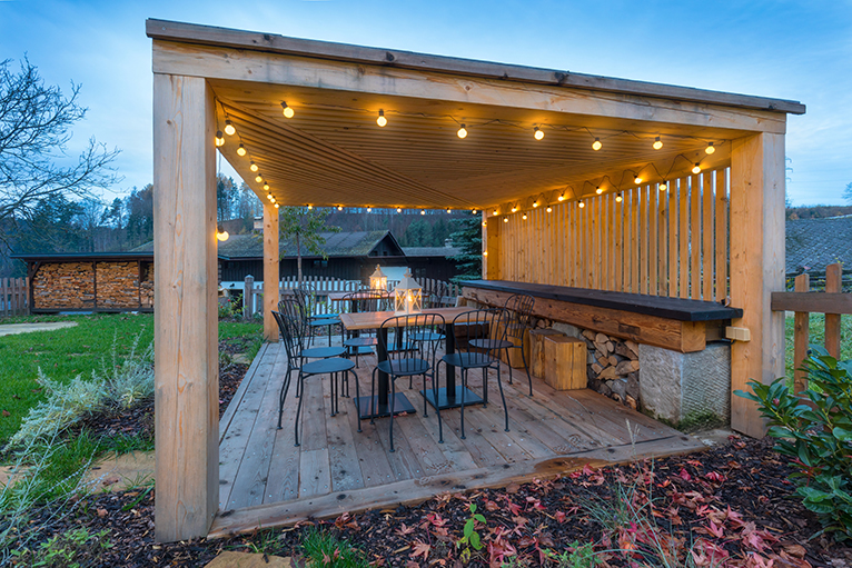 Large wood gazebo with lights on a summer night in all year round garden