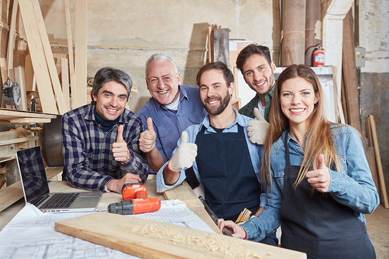 Group of carpenters smiling and putting thumbs up