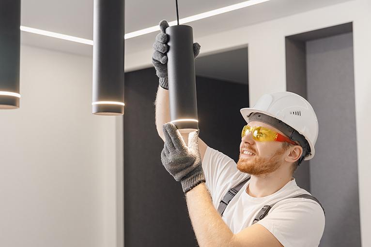 Electrician installing lighting inside home.