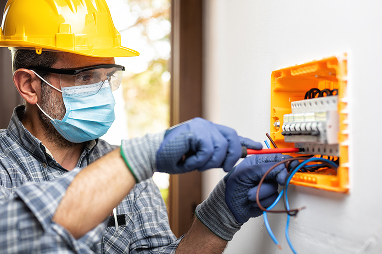 Electrician wearing mask whilst working inside home.