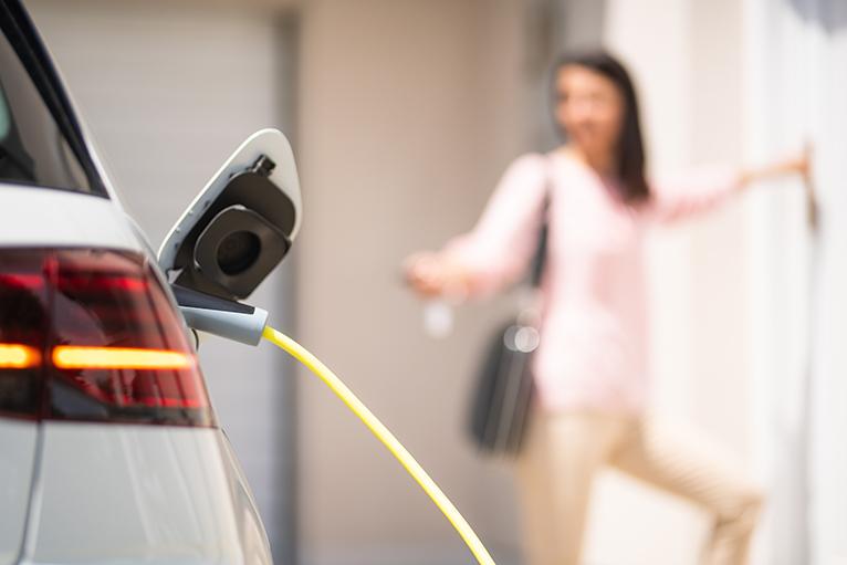 Homeowner charging electric car.
