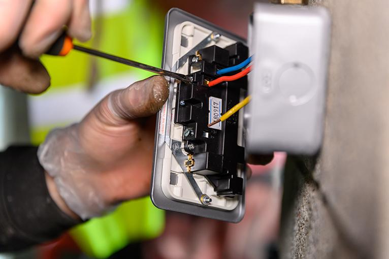Electrician wiring a UK socket plug on garage wall.