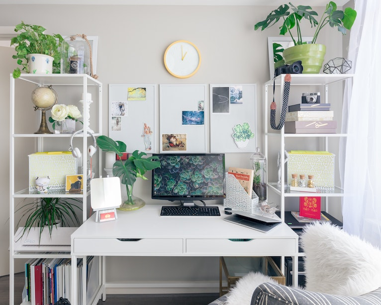 White desk decorated with surrounding plants, artwork and ornaments