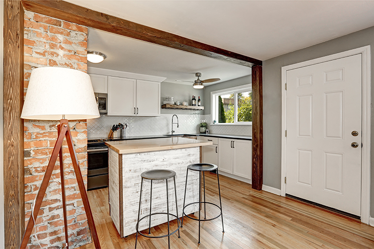 Kitchen with small island and exposed brick interior