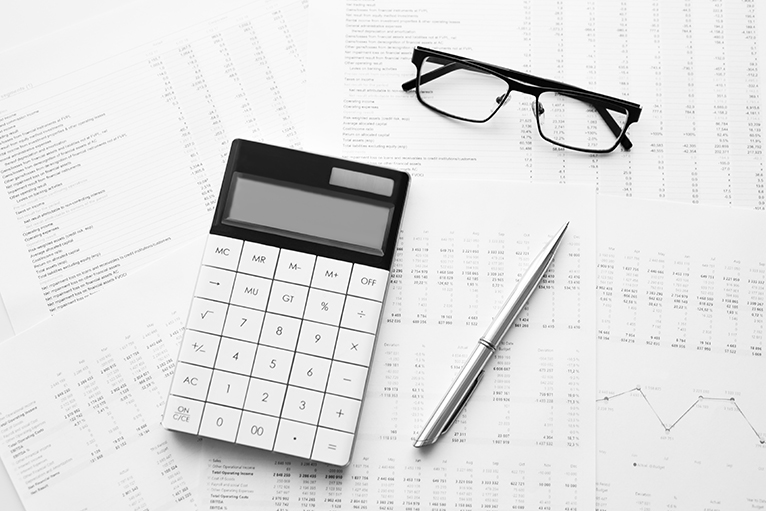 Calculator, pen, glasses and financial documents on table
