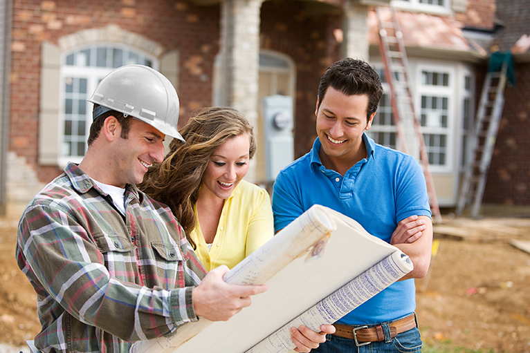 Help to Build: Couple looking at house plans with builder