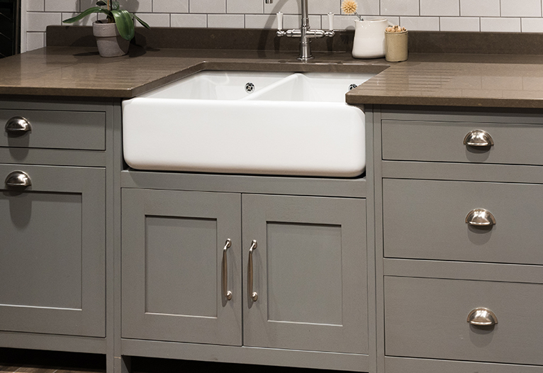 Kitchen makeover hacks: White farmhouse surrounded by grey cabinets with silver handles