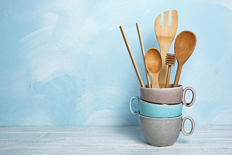 Wooden utensils and mugs against light blue wall
