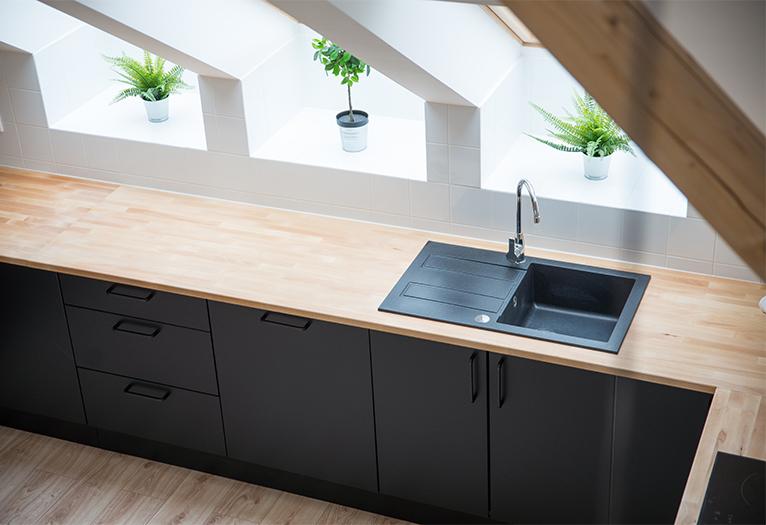 Attic kitchen with black cabinet doors