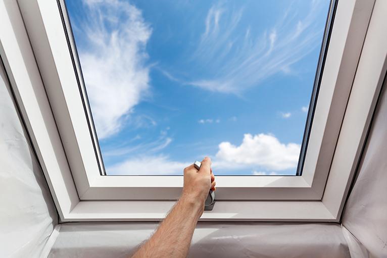 Person opening skylight window in attic