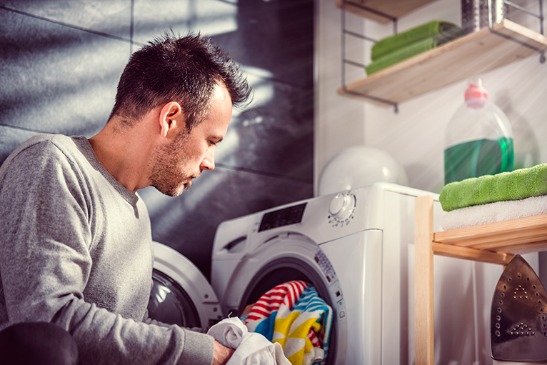 Water efficient home: Person loading laundry in washing machine