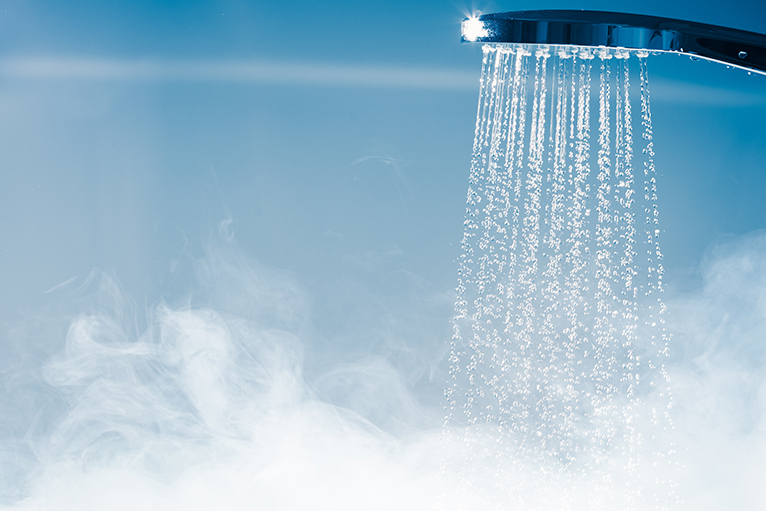 Water efficient home: Running shower with steam rising