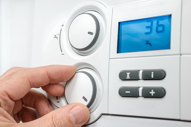 Energy efficiency home grants: Person adjusting heating control panel
