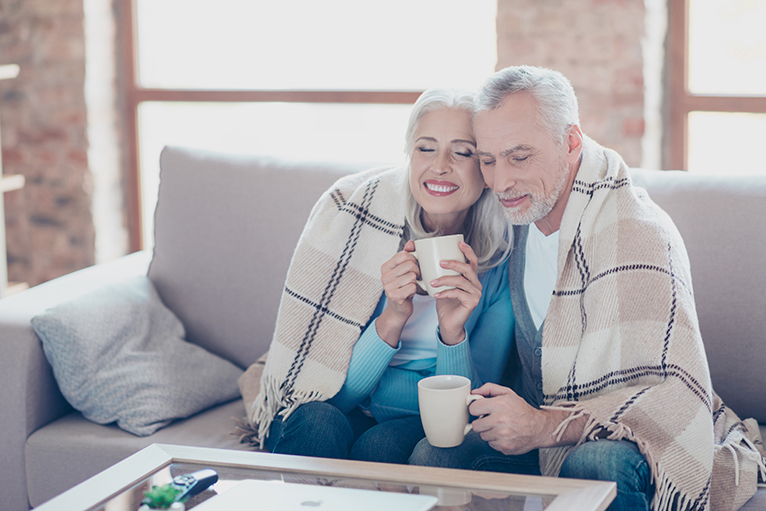 Energy efficiency home grants: Older couple sitting on sofa with blanket and hot drinks
