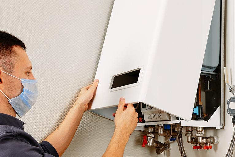 Energy efficiency home grants: Gas/heating engineer repairing boiler whilst wearing mask during the coronavirus pandemic