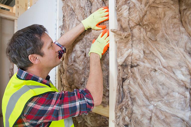 Tradesperson installing wall insulation