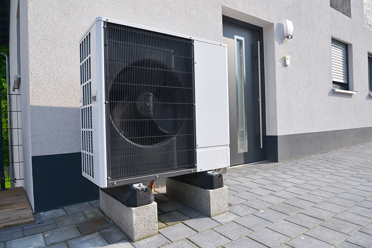 Energy efficiency home grants: Air to air heat pump in front of building