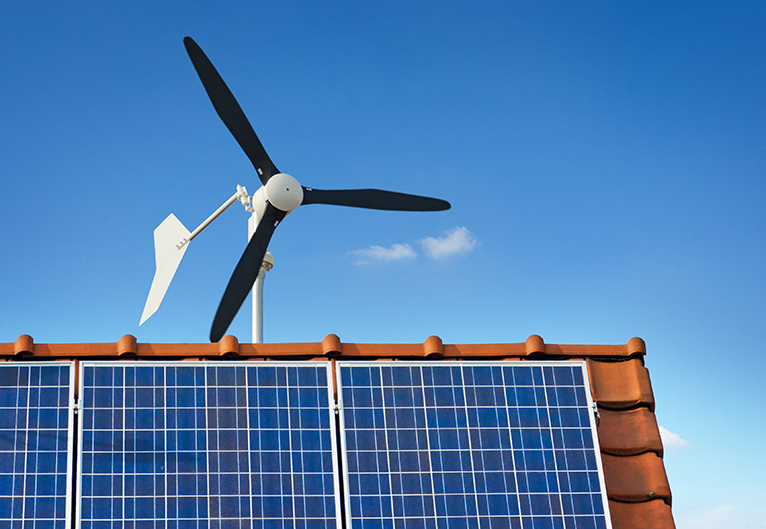 Small wind turbine behind house with solar panels