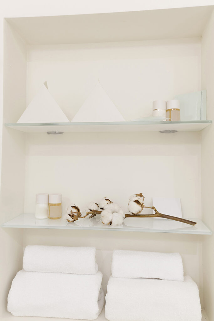 Glass shelves with towels and toiletries