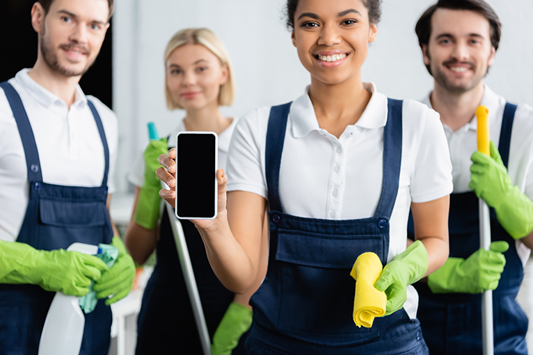 Smiling cleaner holding smartphone