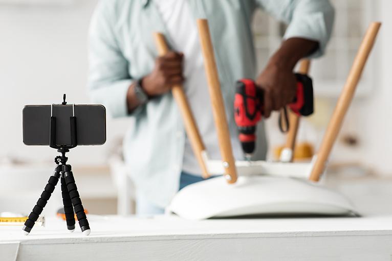 Handyman filming flatpack furniture assembly for social media videos