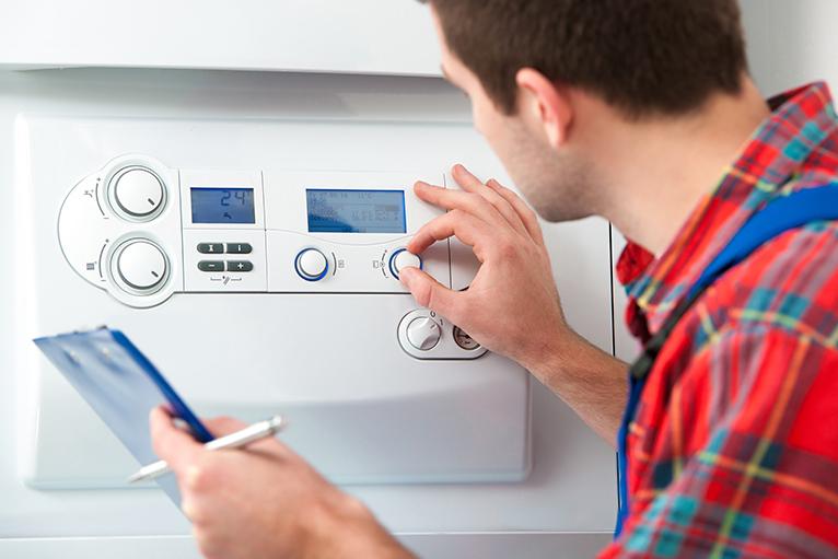 Summer home improvement job ideas: Gas and heating engineer servicing boiler