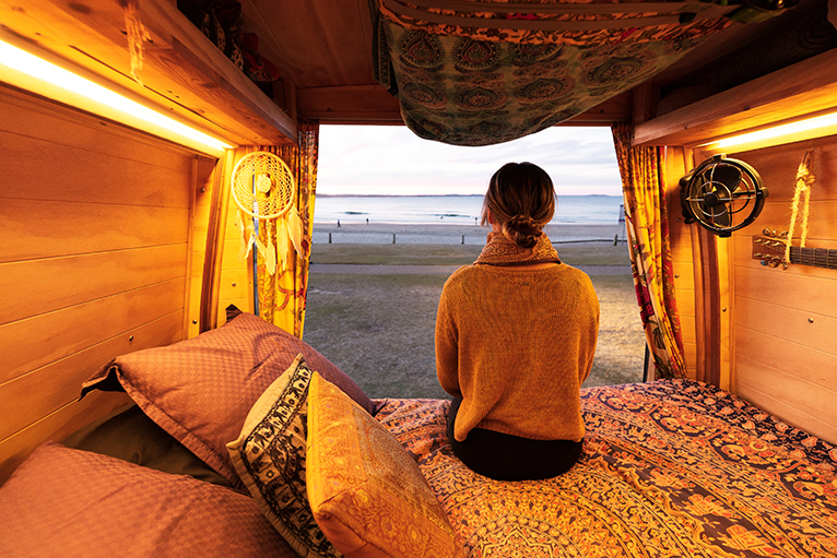 Person watching sunset from campervan