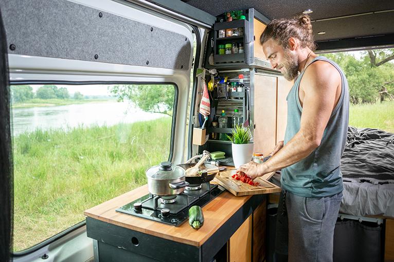 Man cooking in camper van kitchen