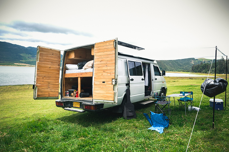 Camper van with fixed bed and storage