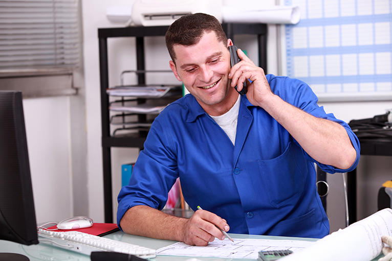 Tradesman using the phone in the office