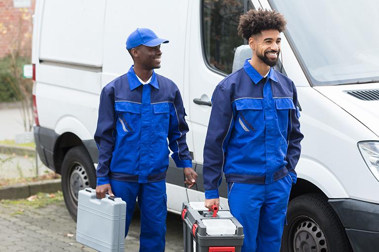 Two tradesmen standing near white van