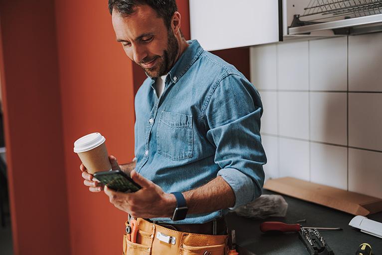 Tradesman smiling at mobile phone