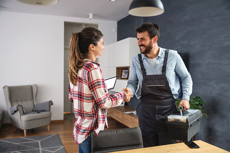 Happy customer shaking hands with handyman and giving a positive online review