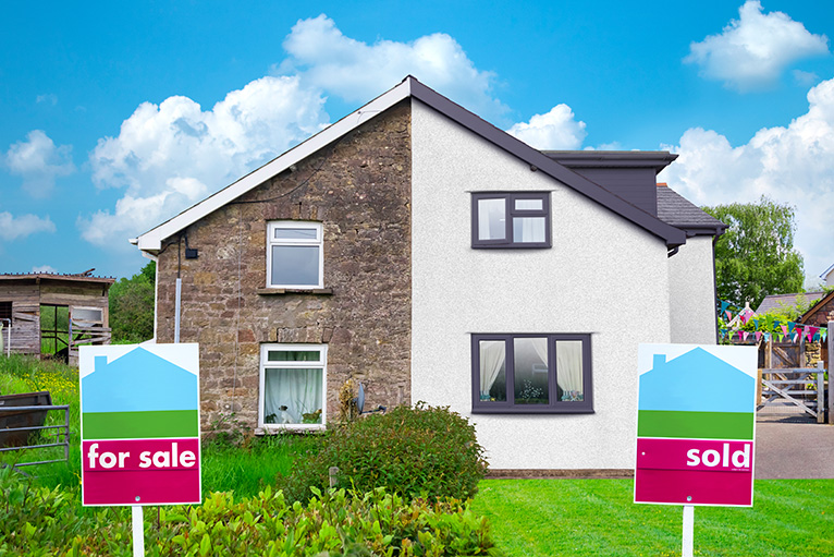 For Sale and Sold signs outside semi detached houses