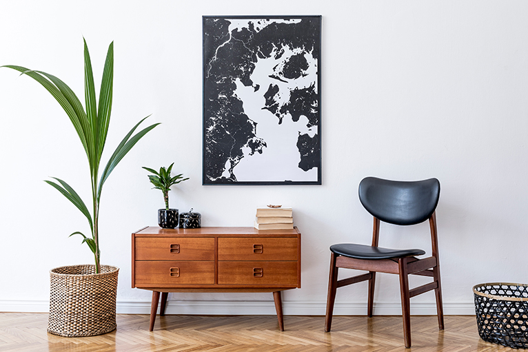 Wooden furniture in room, including retro commode, chair, tropical plant in rattan pot, basket and elegant personal accessories