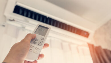 Person adjusting air conditioning with remote
