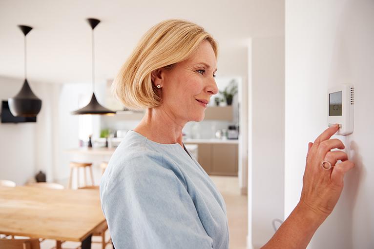 Person adjusting air conditioning temperature