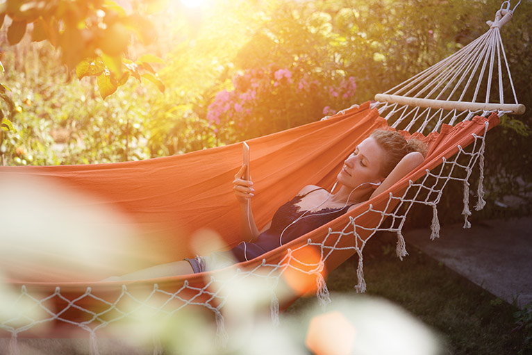 Home security precautions: Woman relaxing in hammock whilst looking at a home security smartphone app
