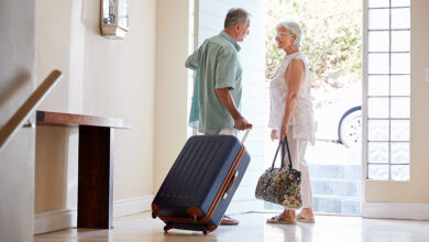 Senior couple leaving home with suitcases to go on holiday