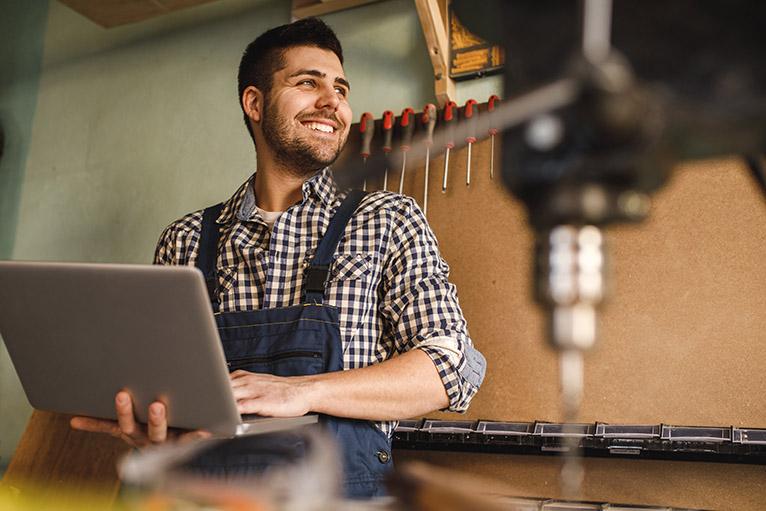 Smiling carpenter in workshop completing business admin on laptop