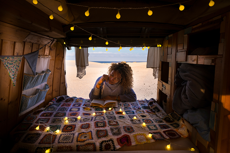 Person reading next to hanging pockets in camper van