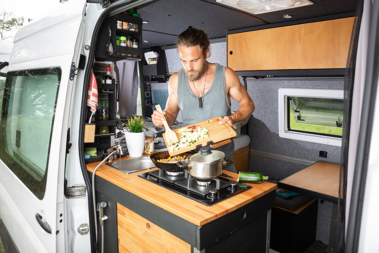 Person using spice rack storage whilst cooking in camper van