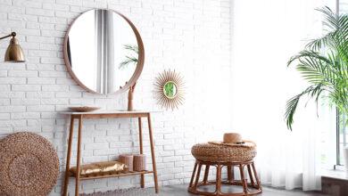 Large round mirror on brick wall in hallway