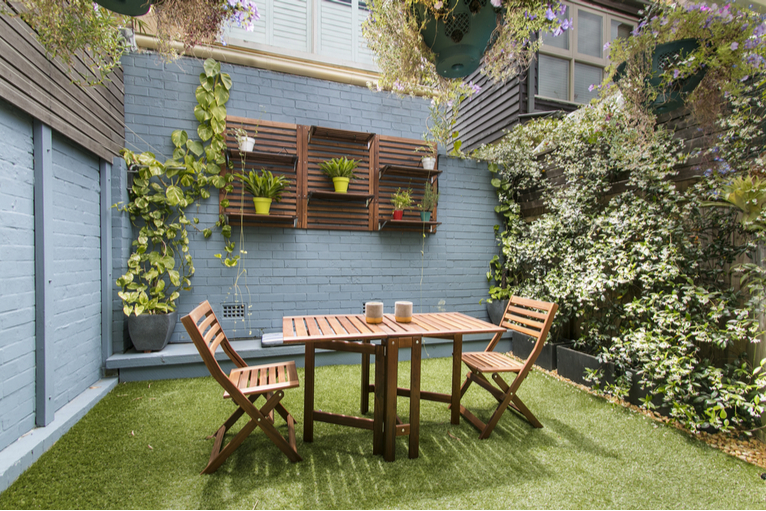Awkward shaped small city garden with outdoor dining set, living wall and astroturf