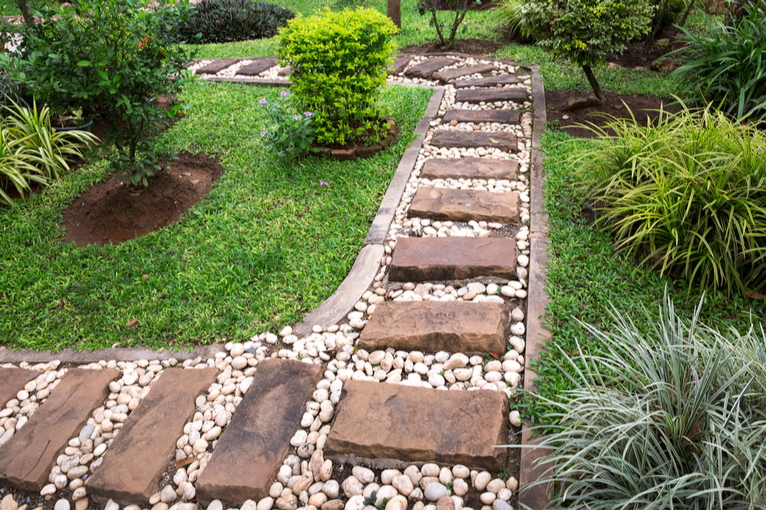 Garden path with stones and plants in edging