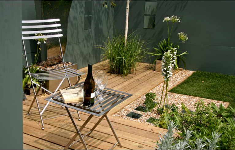 L shaped patio with metal dining set and grassy plants