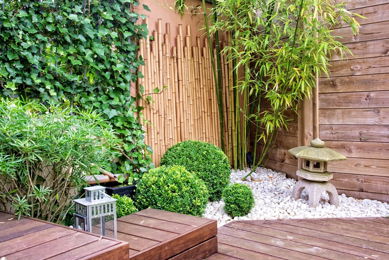 Multi-level garden with bamboo, stone garden ornaments and tall plants