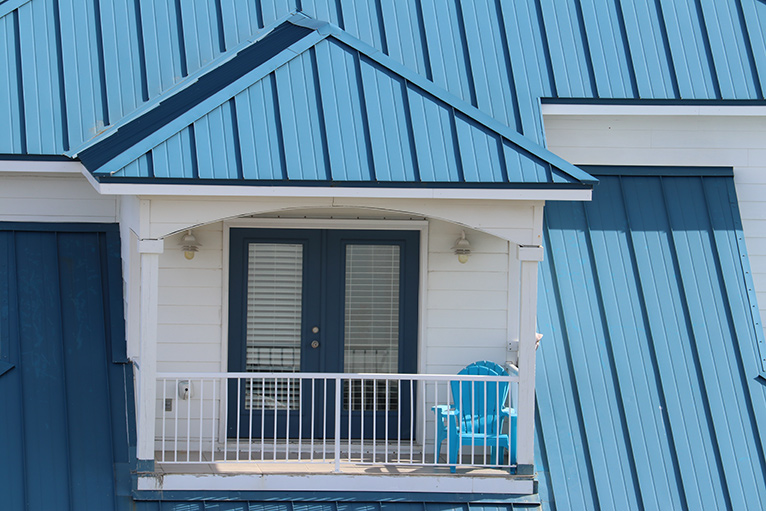 Blue metal roof on beach house with white balcony